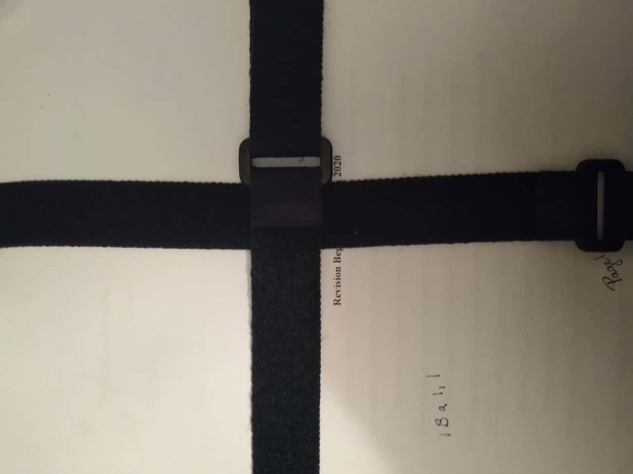 velcro straps fastened across a manuscript, one vertical, one horizontal.
